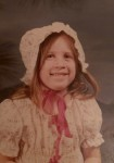 The author at age six, in her bonnet waiting to move to the prairie.